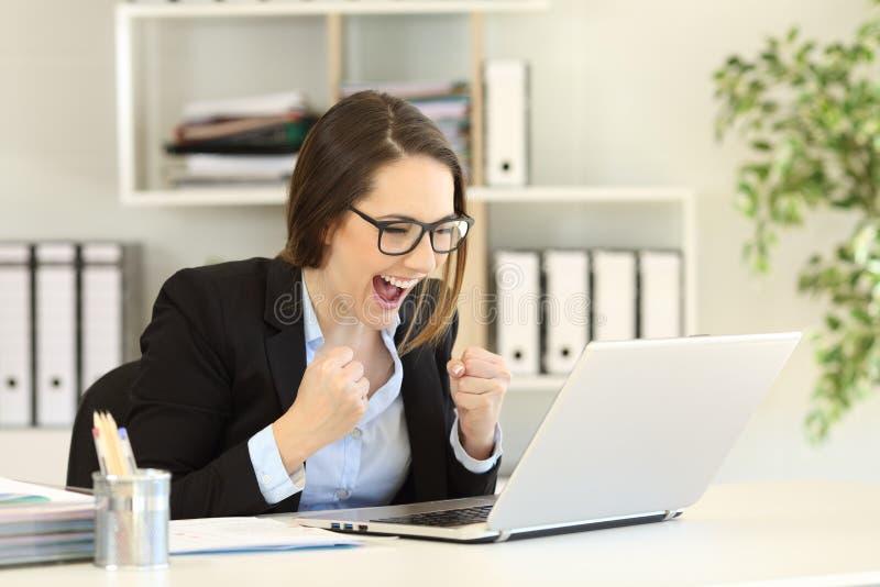 Upphetsad läsande online-nyheterna för kontorsarbetare i en bärbar dator arkivfoton