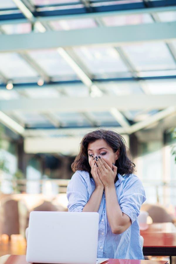 Upphetsad le kvinna som firar online-seger, genom att anv?nda b?rbara datorn i kaf? och att se sk?rmen som skriker med att lyfta  arkivfoto