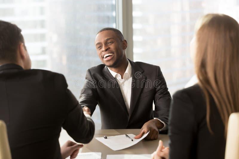 Upphetsad le vit partner för svart affärsmanhandshaking på M royaltyfri foto