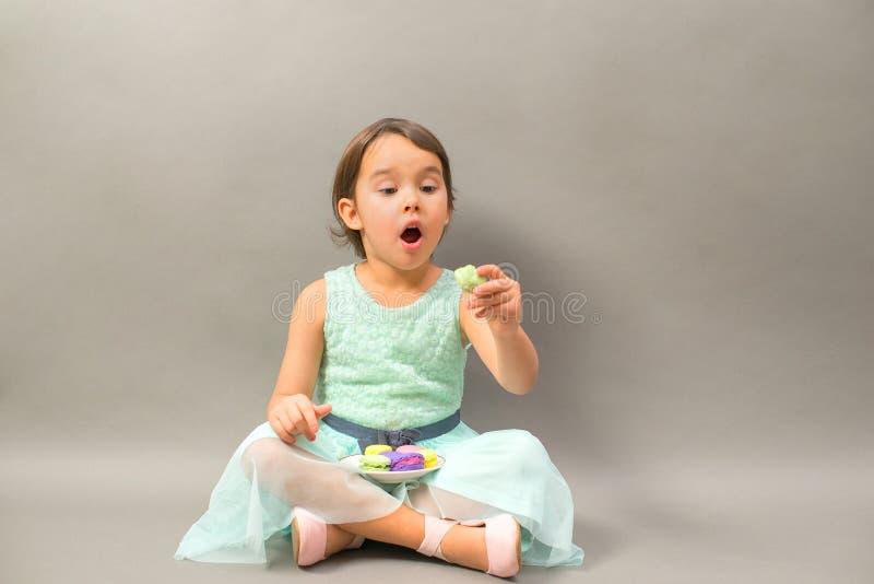 Upphetsad liten flicka med en platta som är full av makron arkivfoto
