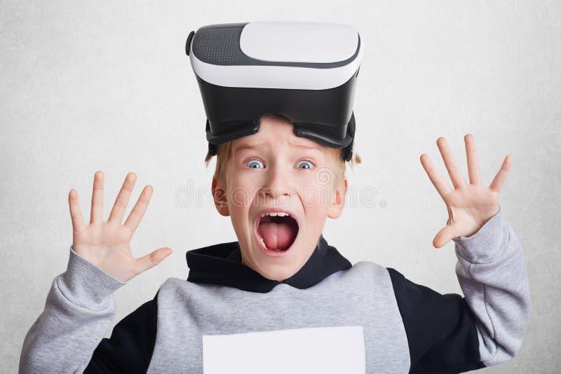 Upphetsad liten pojkehandlagluft under VR-erfarenhet Det lilla barnet bär virtuell verklighethörlurar med mikrofon på huvudet, un royaltyfri bild