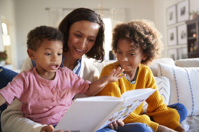 Upphetsad litet barnpojke som sitter på hans mother�sknä som läser en bok i vardagsrummet med hans äldre syster, slut upp arkivfoto