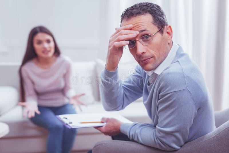 Upphetsad litet trött psykolog som ser i väg från hans klient royaltyfri foto