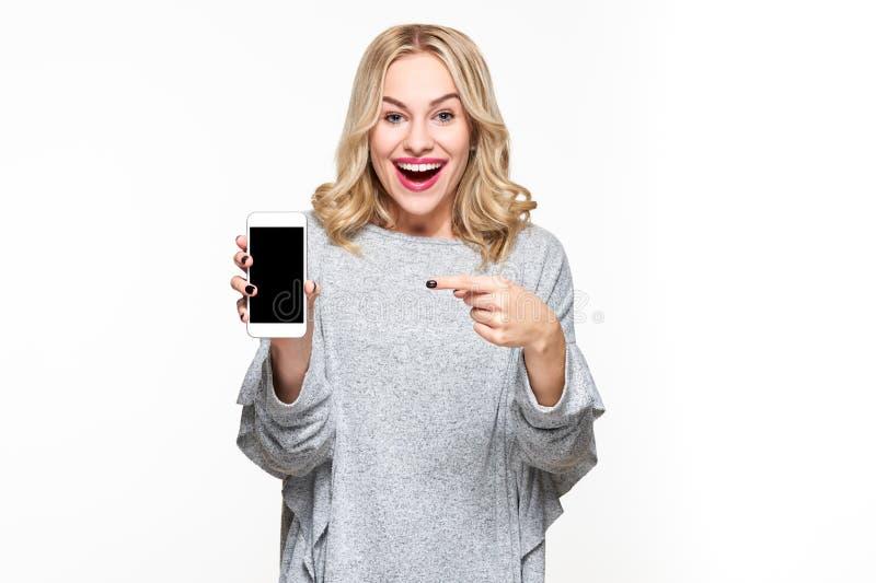 Upphetsad lycklig blond kvinna i skärm för smartphone för tröjavisningmellanrum och peka på den, medan se kameran med den öppna m arkivfoton