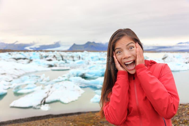 Upphetsad lycklig kvinna på glaciärlagun på Island royaltyfri bild