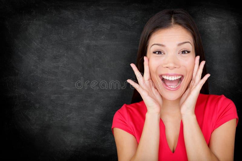 Upphetsad lycklig kvinna vid svart tavla/den svart tavlan royaltyfri foto