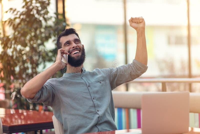 Upphetsad lycklig skäggig freelancer som läser emailen med resultat om seger i den moderna online-striden som sitter på bärbara d arkivbilder