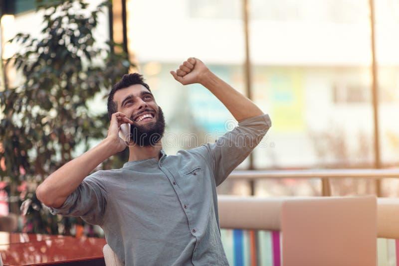 Upphetsad lycklig skäggig freelancer som läser emailen med resultat om seger i den moderna online-striden som sitter på bärbara d arkivbild