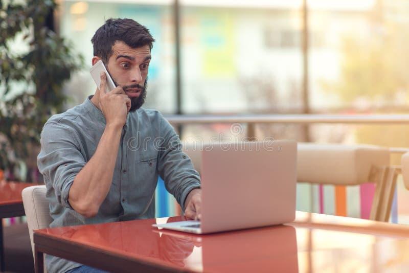 Upphetsad lycklig skäggig freelancer som läser emailen med resultat om seger i den moderna online-striden som sitter på bärbara d royaltyfri bild