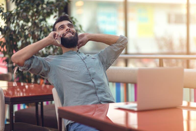 Upphetsad lycklig skäggig freelancer som läser emailen med resultat om seger i den moderna online-striden som sitter på bärbara d royaltyfria bilder