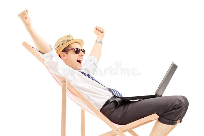 Upphetsad man med bärbar datorsammanträde på en strandstol royaltyfri fotografi