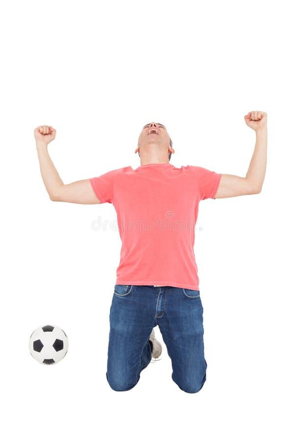 Upphetsad man som ropar med näven upp och en fotbollboll royaltyfri foto