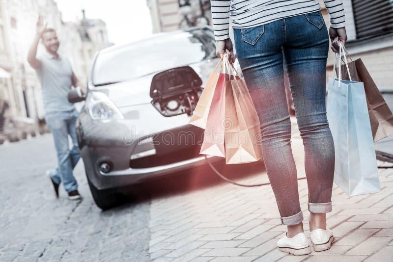 Upphetsad man som vinkar till hans flickvän som går tillbaka från shopping arkivbild