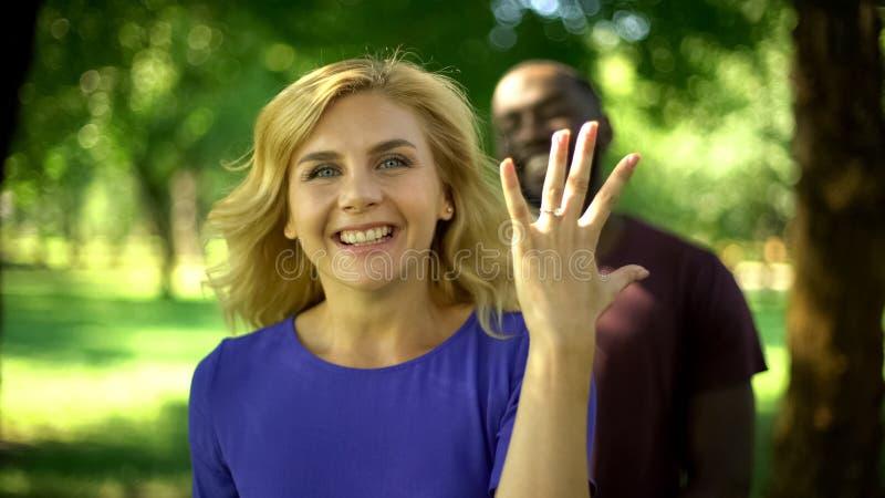 Upphetsad nätt kvinnavisningförlovningsring, mellan skilda raser förbindelse, lycka arkivfoto