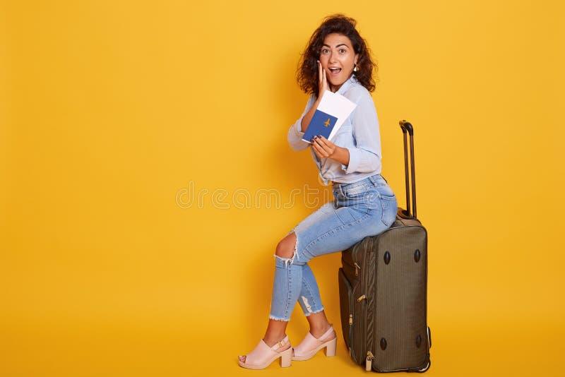Upphetsad och lycklig ung gladlynt kvinnlig turist som sitter på hennes stora resväska och rymmer passet med flygbiljetter som är arkivbilder