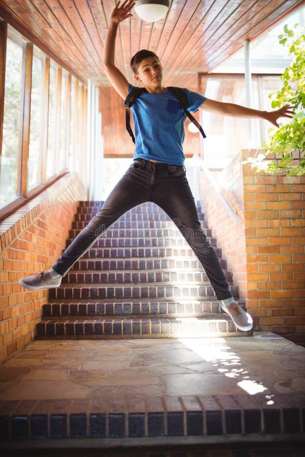 Upphetsad pojke som hoppar nära trappuppgång på skolan fotografering för bildbyråer