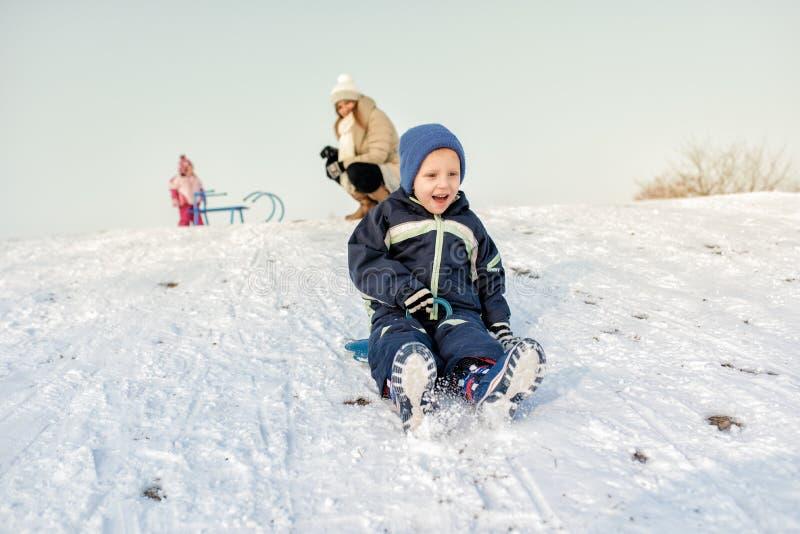 Upphetsad pys på snö som tobogganing arkivbilder