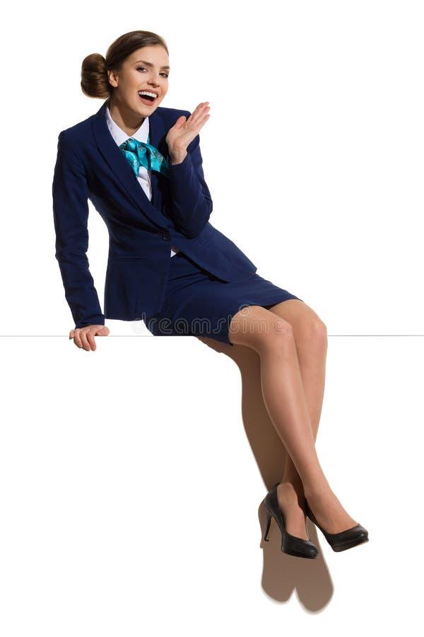 Upphetsad stewardess Sitting On en överkant av banret arkivfoton