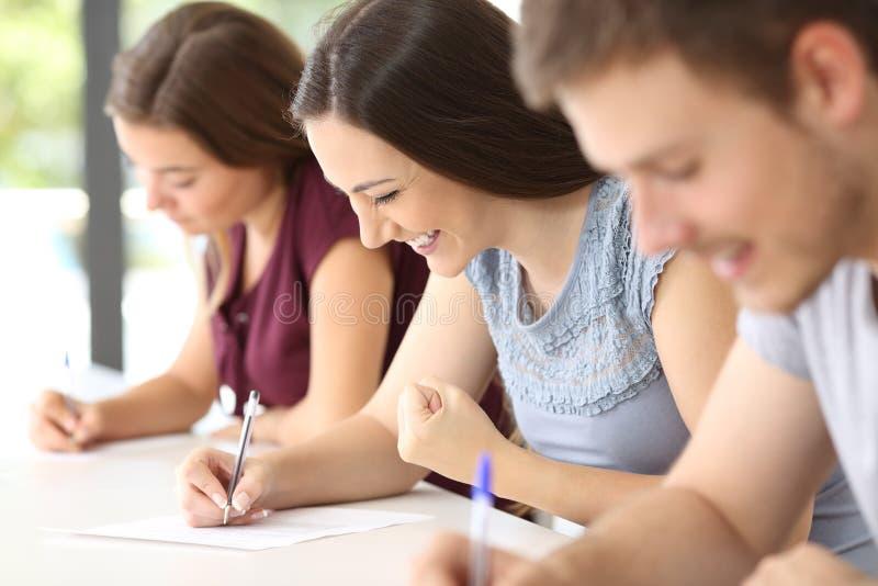 Upphetsad student under en examen på klassrumet arkivfoto