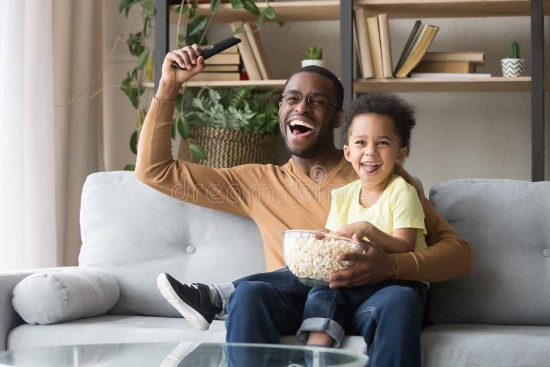 Upphetsad svart fader med leken för tv för sport för litet barnson den hållande ögonen på royaltyfria bilder