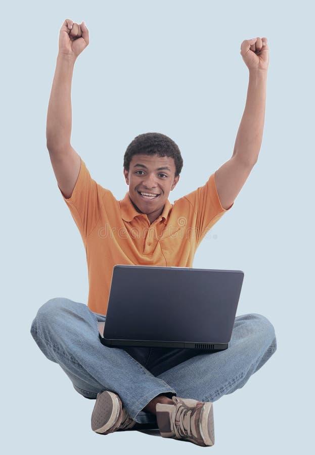 Upphetsad svart man med en bärbar dator - som isoleras över en vit arkivfoto