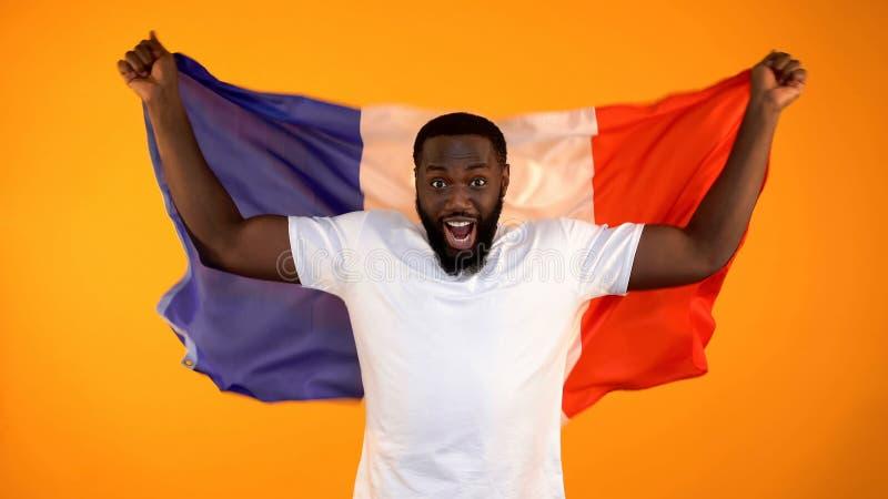 Upphetsad svart man som rymmer den franska flaggan, st?ttande nationellt sportlag som hurrar royaltyfri foto