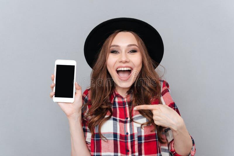 Upphetsad tillfällig kvinna som pekar fingret på mobiltelefonen för tom skärm royaltyfri bild