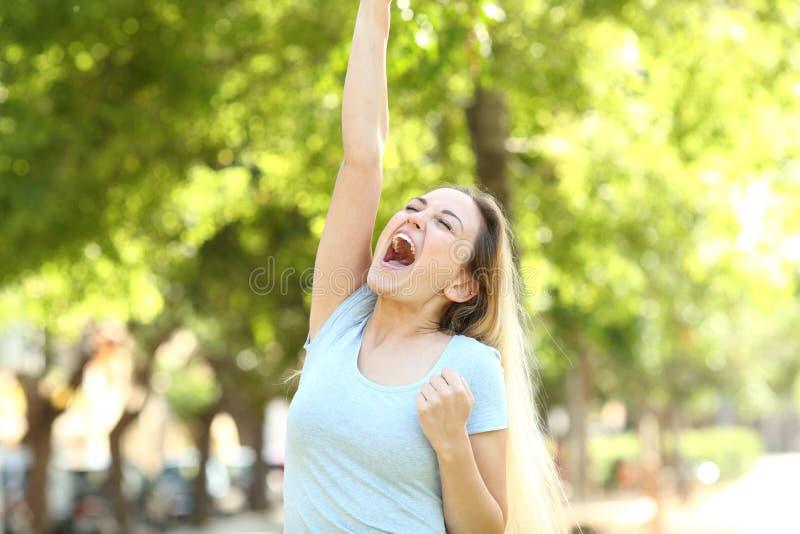 Upphetsad tonårs- flicka som lyfter armen som firar framgång arkivbild