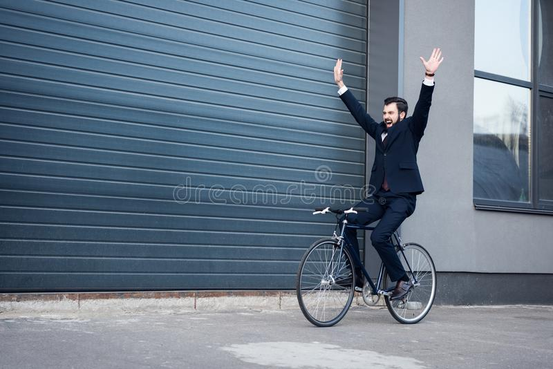 upphetsad ung affärsman med utsträckta armar som rider cykeln arkivfoton