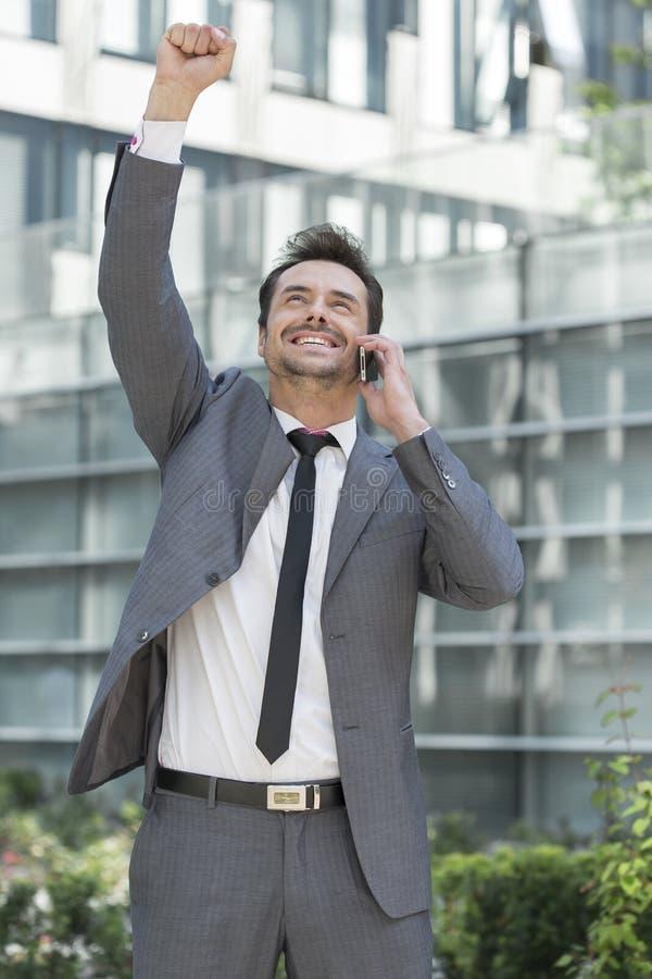Upphetsad ung affärsman som använder mobiltelefonen utanför kontor arkivfoton
