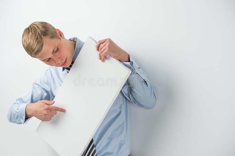 upphetsad ung affärsman som rymmer ett tomt bräde royaltyfri bild