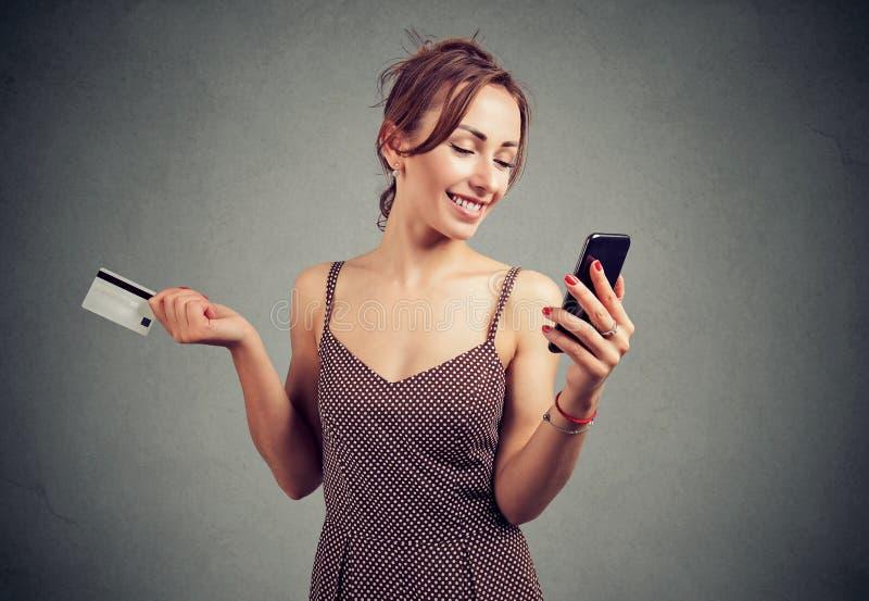 Upphetsad ung dam som använder den hållande kreditkorten för mobiltelefon royaltyfria bilder