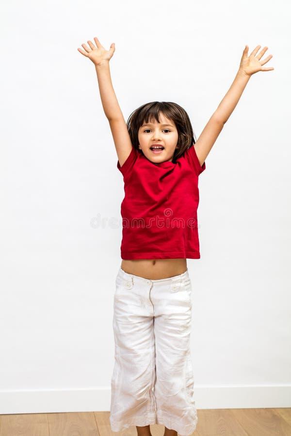Upphetsad ung härlig flicka som högt hoppar och lyfter henne armar royaltyfria foton