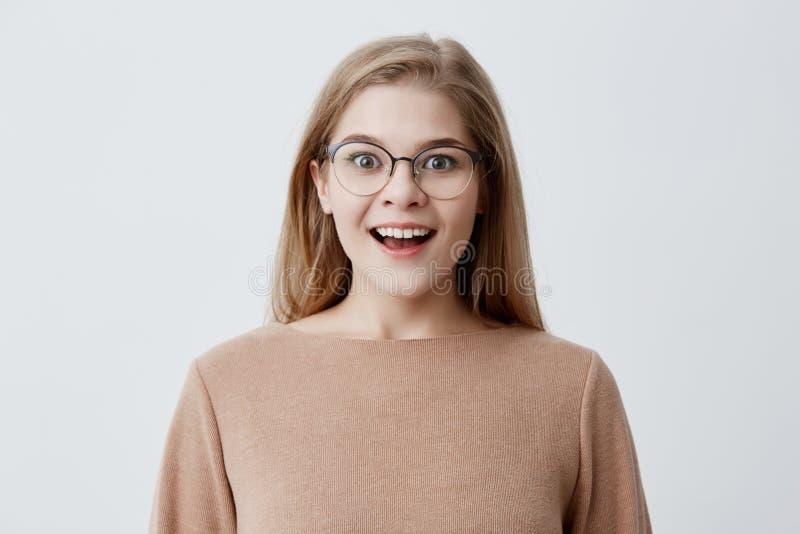 Upphetsad ung kvinna av den europeiska utseendemässiga bärande lösa tröjan för brunt, med blont hår, i glasögon som i huvudsak le fotografering för bildbyråer