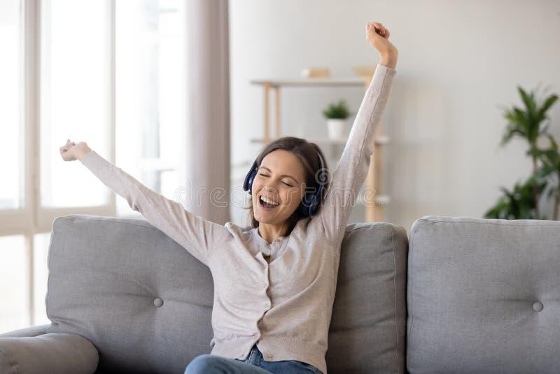Upphetsad ung kvinna i hörlurar som hemma tycker om favorit- musik arkivfoto