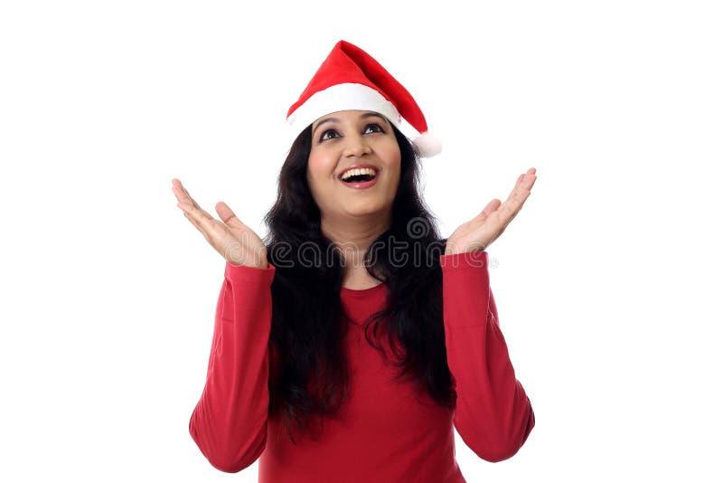 Upphetsad ung kvinna i jultomtenhatt royaltyfri foto