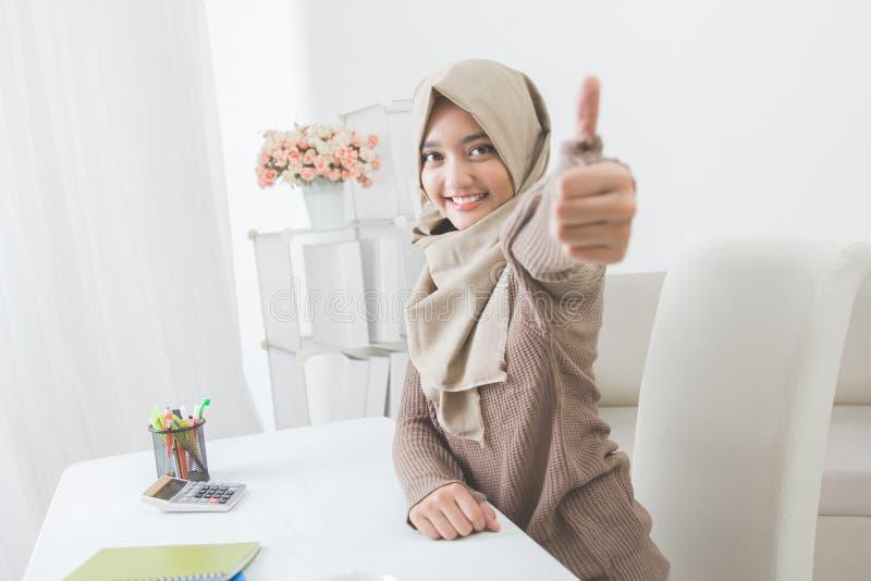 Upphetsad ung kvinna med hijab som ler till kameran och visar thu fotografering för bildbyråer