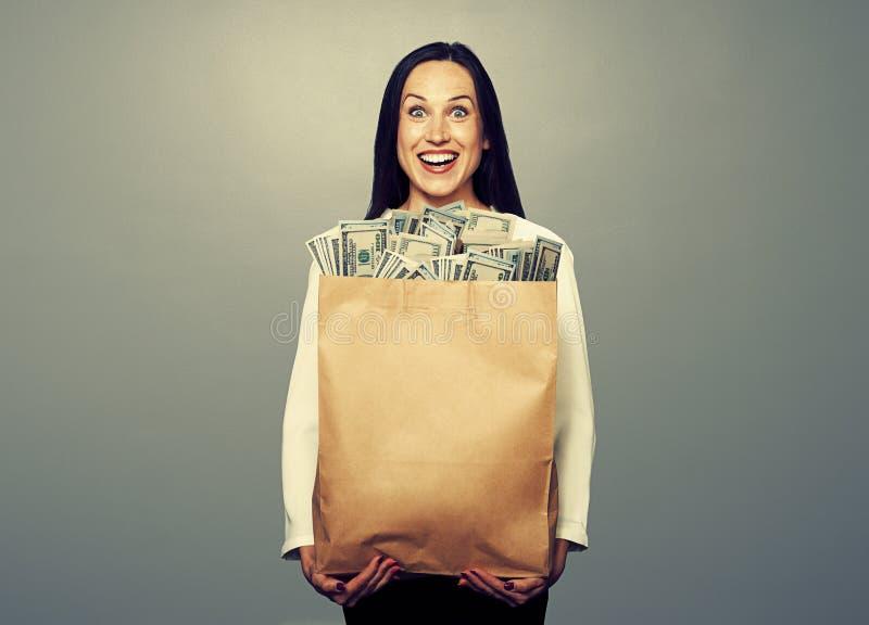 Upphetsad ung kvinna med pengar arkivfoto