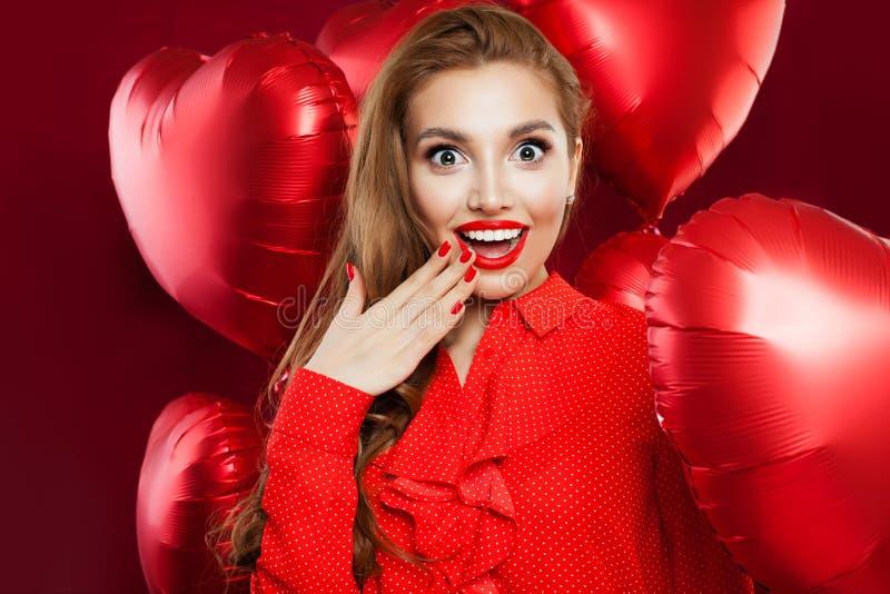 Upphetsad ung kvinna med röda hjärtaballonger Den förvånade flickan med röd kantmakeup, långt lockigt hår andExcited flickan på r royaltyfri fotografi