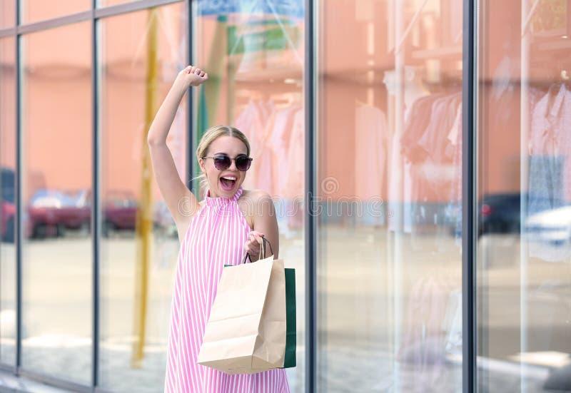 Upphetsad ung kvinna med shoppingpåsar på stadsgatan royaltyfri foto