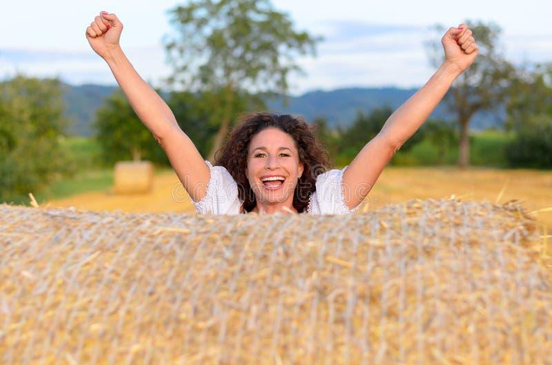 Upphetsad ung kvinna som firar i ett lantgårdfält arkivfoton