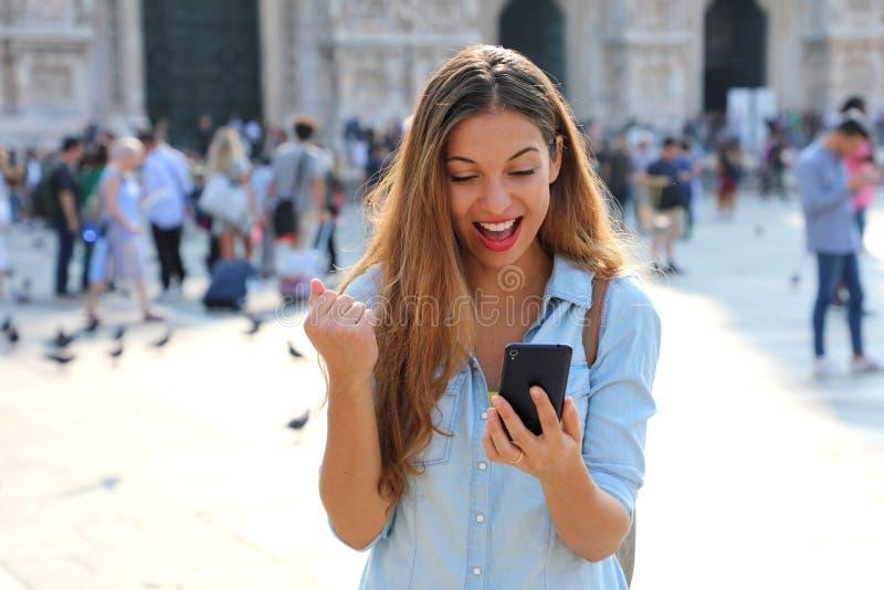 Upphetsad ung kvinna som mottar goda nyheter på linje i en smart telefon royaltyfri bild