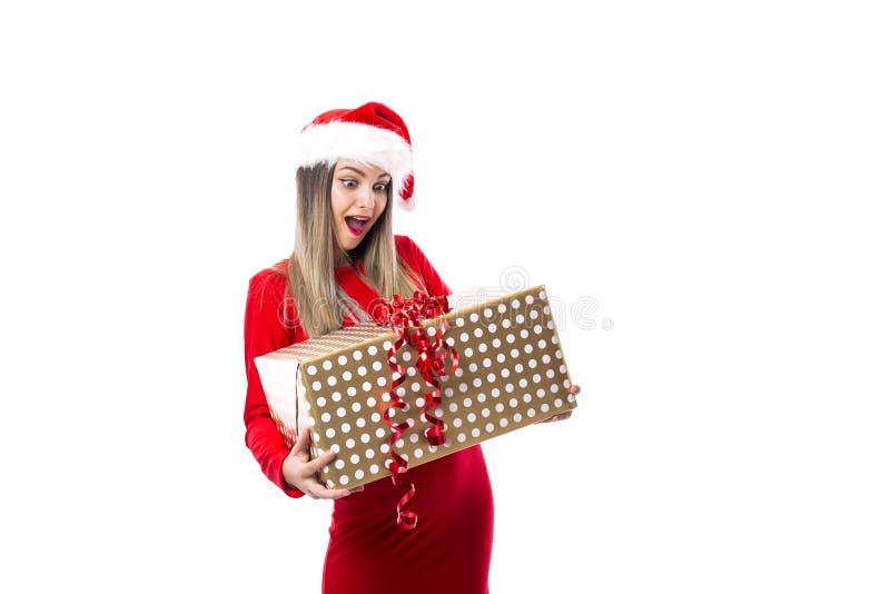 Upphetsad ung kvinna som rymmer en stor gåva över vit arkivfoto