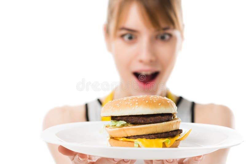 upphetsad ung kvinna som ser hamburgaren på plattan arkivbild