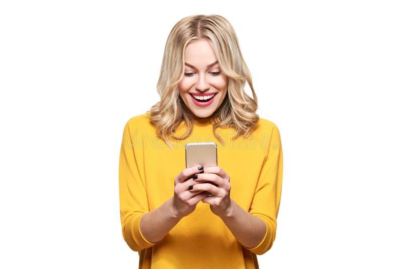 Upphetsad ung kvinna som ser hennes le för mobiltelefon Meddelande för kvinnaläsningtext på hennes telefon som isoleras över vit royaltyfri fotografi