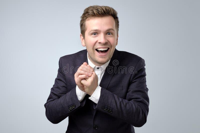 Upphetsad ung man som firar framgång luft och applådhänderna på den gråa bakgrunden fotografering för bildbyråer
