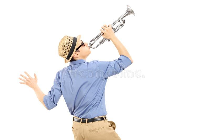 Upphetsad ung musiker som spelar trumpeten arkivfoto