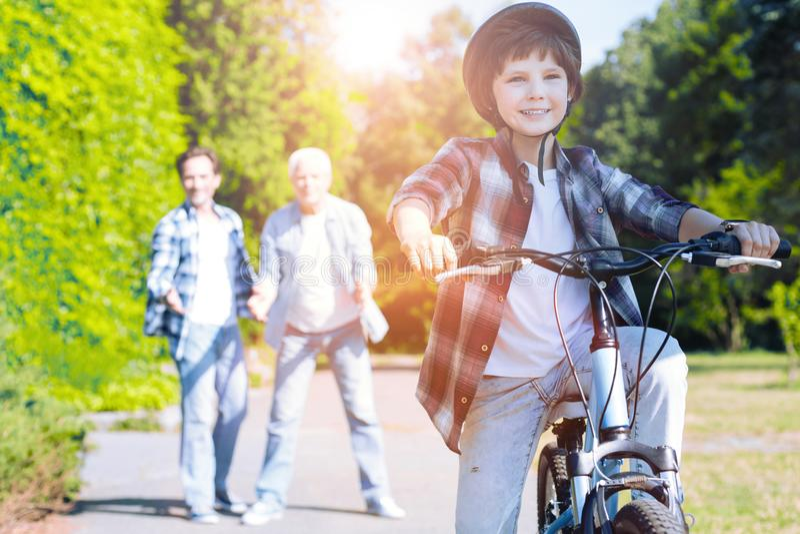 Upphetsad unge som lär att rida cykeln utomhus royaltyfri bild