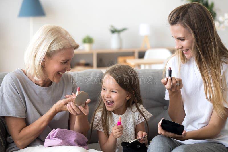 Upphetsad ungeflicka som rymmer läppstift som gör makeup med mammamormodern royaltyfri fotografi