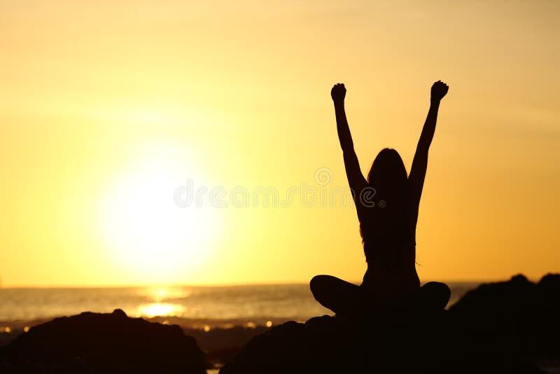 Upphetsad upprymd kvinna som ser solen på soluppgång arkivbilder